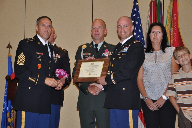 Sergeant Maj. David L. Baade, Headquarters & Headquarters Battalion (second from left), poses for a photo with Command Sgt. Maj. Jesus Ruiz, command sergeant major, 25th Combat Aviation Brigade (left); his wife Claudia and son Maximilian; and Col. Frank Tate, commander, 25th CAB, during the 25th Infantry Division Quarterly Retirement Ceremony on Schofield Barracks, Hawaii, Nov. 17. Baade retires from Active duty with 25 years of service.