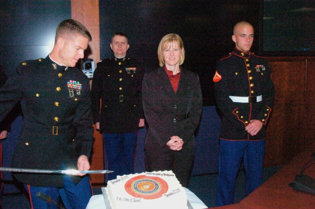 Maj. Thomas Favor, J35 prepares to cut another piece of the Marine Corps 235th birthday cake and pass it to the oldest Marine attending the ceremony retired Capt. Teresa Ovalle, Public Affairs who will then pass it to the youngest Marine Lance Cpl. Justin Carney, Marine Corps Barracks 8th and I.