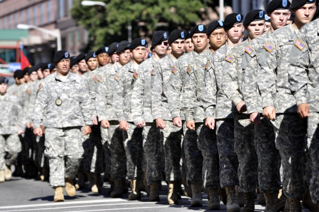 Staff Sgt. Adam Arruda, 187th Ordnance Battalion, marches with the battalion's Soldiers in the City of Columbia's Veterans Day parade Nov. 11. Right, retired Col. Charles Murray interacts with the crowd during the parade. Murray, who received the Medal of Honor for his actions in World War II, served as the parade marshal.