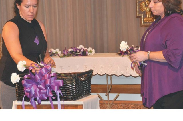 Army Community Service volunteer Natascha Duvall, left, and Stacie Beard, a prevention specialist with SARC, Inc., right, place white carnations in a basket during the Domestic Violence Awareness Month candlelight vigil at the Aberdeen Area Chapel Oct. 27.
