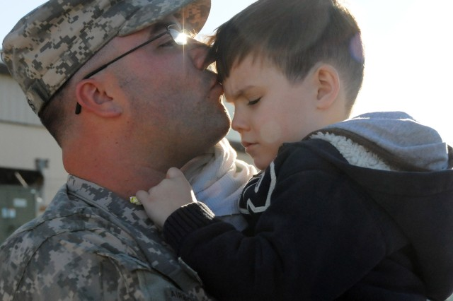 Spc. Keith Torres, 597th Maint. Co. air traffic control equipment repair specialist, gives his son, Brendon, 4, a kiss before departing from Knox Army Heliport to the Middle East.