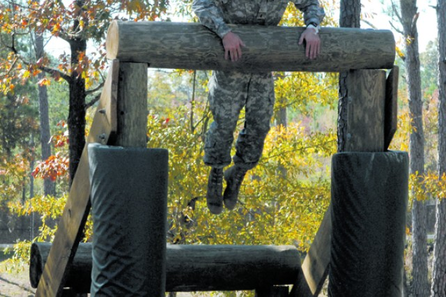 1st Lt. John Ubriaco from Fort Benning jumps high on the Dirty Name obstacle.