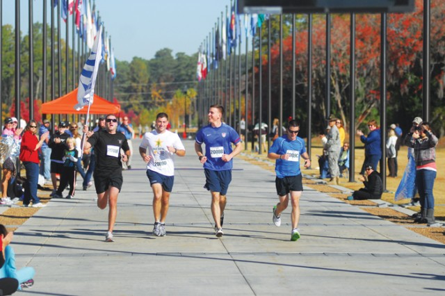 Edward Guelfi, Robert Huefner, Jared Wigton and Joshua McCarver race down Heritage Walk to the finish line Saturday to complete the relay marathon run. Elijah Phillips (not pictured) ran the first leg.