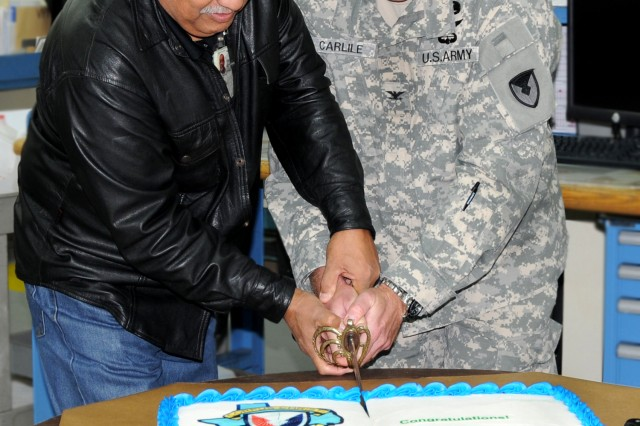 T-55 Engine Shop subassembly shop supervisor, Art PonceDeLeon and Col. Christopher Carlile, CCAD Commander, cut the cake Air Assault style with the depot's saber during the event celebrating the 400th T55-GA-714 Engine overhauled at the depot.