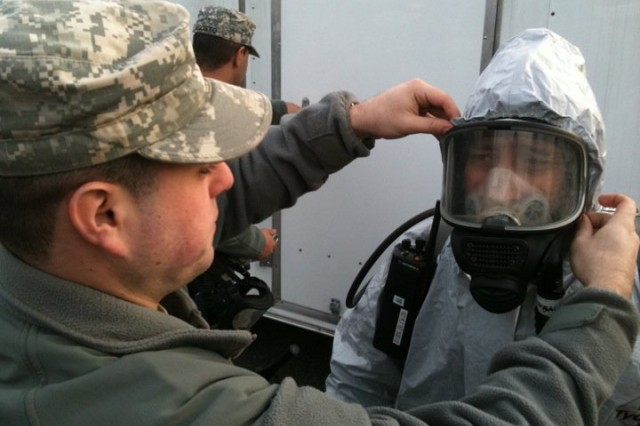POMONA, NY--New York Army National Guard 2nd Lt. Roman Rushlion, Recon Platoon Leader with the 222nd Chemical Company, Brooklyn, NY, fits a chemical protective mask on a Soldier ready to go into the exercise site to  place chemical detectors. More than 400 members of the New York Army and Air National Guard, along with volunteers of the New York Guard, the state defense force participated in the weekend exercise along with civilian first responders.   The training event tested the skills of the Guard force that is specially trained to rescue victims from contaminated buildings, decontaminate them, and provide medical treatment, and also exercised New York National Guard command and control systems and logistics.