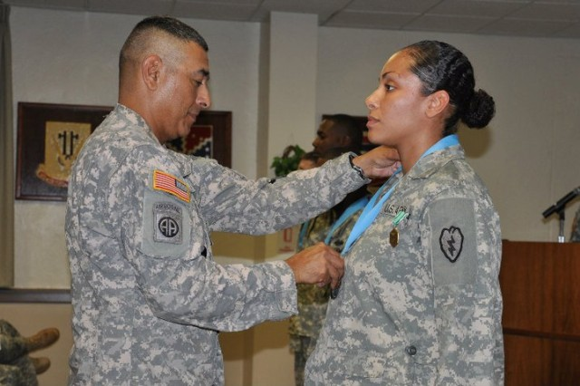 Staff Sgt. Melinda Quinones, Company C., 325th Brigade Support Battalion, 3rd Brigade Combat Team, 25th Infantry Division, receives Sgt. Audie Murphy Club Medallion from Command Sgt. Maj. Frank M. Leota, 25th Inf. Div. command Sgt. Maj. during the 25th Inf. Div. Sgt. Audie Murphy Club Induction Ceremony Nov. 18 at the Main Post Conference Room, Schofield Barracks, Hawaii. The award was given to non-commisioned officers who showed a significant leadership and performance achievements during a selection board that was held on Oct. 27.