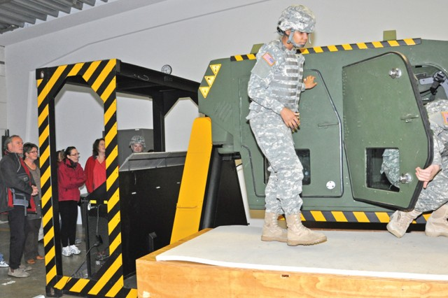 Educators watch as Soldiers exit from a vehicle rollover simulator (or HEAT for High Mobility Multipurpose Wheeled Vehicle Egress Assistance Trainer) during the orientation tour of the Wiesbaden Training Support Center.
