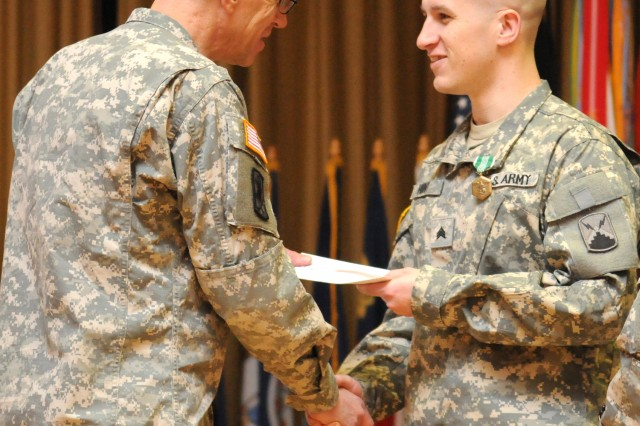 WIESBADEN, Germany (Nov. 22, 2010) -- Brig. Gen. Jeffrey G. Smith, Jr. (left), commander, 5th Signal Command, presents Sgt. Edwin Hunt, 69th Signal Battalion, with gift certificates during the 2010 Soldier and Noncommissioned Officer of the Year ceremony held at the Taunus Theater. Hunt won NCO of the Year following a competition that tested NCOs and Soldiers throughout 5th Signal Command with a physical fitness test, Warrior Task skills, a firing range, followed by a questionnaire-style board, where the competitors answer difficult military questions while in their Class A Service Dress uniforms.Smith and Command Sgt. Maj. Marilyn Washington, 5th Signal Command, presented Hunt and Sgt. Cesar Cobena, the NCO and Soldier of the year with gifts donated by sponsors from the Wiesbaden community for their accomplishments.