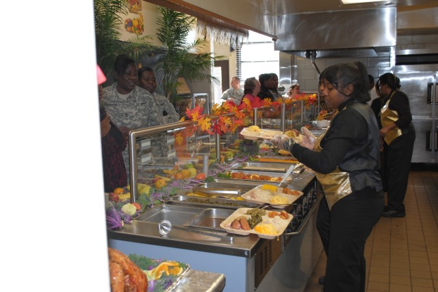 """Shana Howell, an attendant with the Drill Sergeant School dining facility, serves Soldiers during a Thanksgiving feast Wednesday at the facility. This year's Thanksgiving theme for the DFAC was """"Thanksgiving Past and Present."""""""