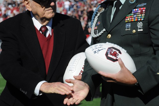 "Master Sgt. Peter Lara, the Army Times 2009 Soldier of the Year, prepares to shake hands with World War II veteran Byron ""Gene"" Burns. They were among the five veterans honored during halftime."