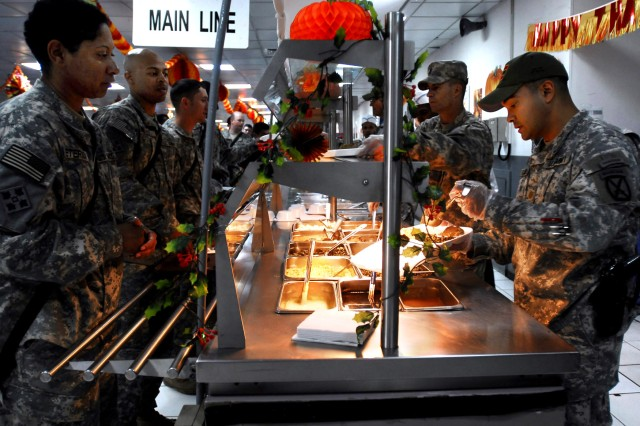 Maj. Jose Polanco serves up dinner during the 2008 Thanksgiving meal in Iraq.