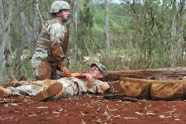 First Lt. Howell Horner, platoon leader, B Company, 2nd Squadron, 6th Cavalry Regiment, 25th Combat Aviation Brigade, communicates with a fellow squad member while providing tactical field care during the 25th CAB's CLS training and qualification field training exercise at Wheeler Army Airfield, Nov. 18.