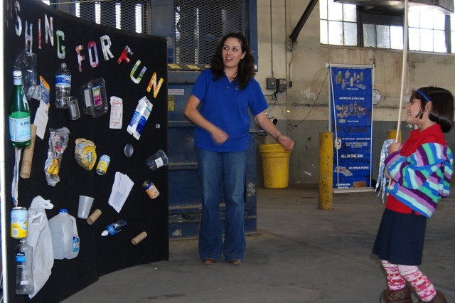 "Stephanie Nebhan, left, Outreach Coordinator for the Fort Bliss Recycling Center gives an expectant look as a young fisher gets a ""bite"" on her line while ""fishing for fun,"" during America Recycles Day at the Fort Bliss Recycling"