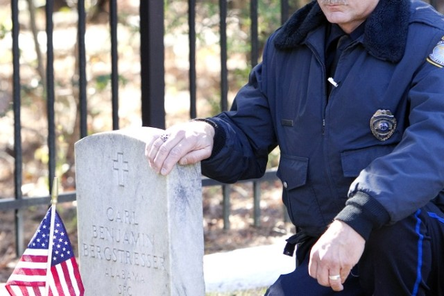 Norbert Bergstresser kneels beside his father's headstone at McClellan's Veterans Cemetery.