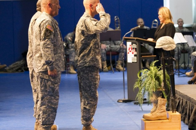 Maj. Jeffery Lewis and the US Army Recruiting Command place a Fallen Soldier Battle Cross in front of the stage at the Physical Fitness Center during Anniston Army Depot's Veterans Day Ceremony Nov. 9.