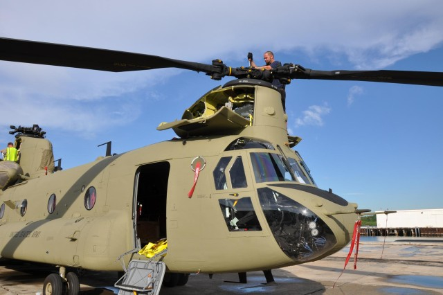 A contactor from Boeing assembles the forward main rotor of a new CH-47F Chinook helicopter at Joint Base Pearl Harbor- Hickham's pier 3 - 5 in Honolulu, prior to taking off for Wheeler Army Airfield Nov. 19.