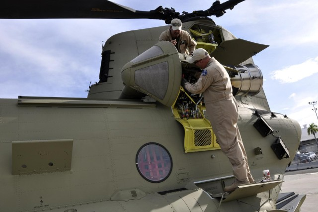 Contractor cargo pilots perform pre-flights checks and inspections on a new CH-47F Chinook helicopter at Joint Base Pearl Harbor- Hickham's pier 3 - 5 in Honolulu, prior to taking off for Wheeler Army Airfield Nov. 19.