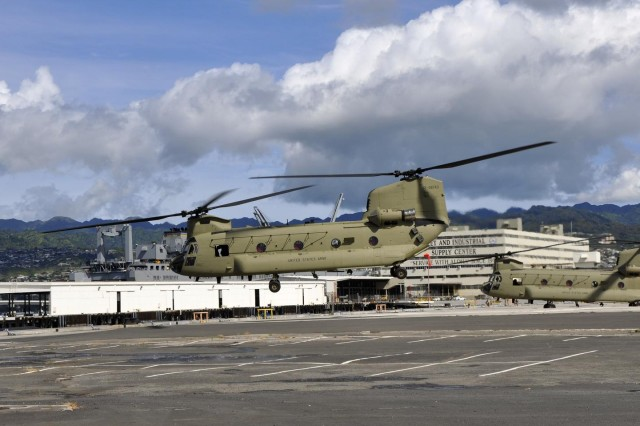 Two new CH-47F Chinook Helicopters take off from Joint Base Pearl Harbor- Hickham's pier 3 - 5 in Honolulu, up the hill to Wheeler Army Airfield on Nov. 19.