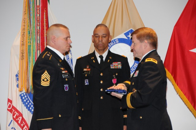 Sgt. Maj. William Kaundart (left) presents the U.S. Flag during the reading of Old Glory to Brig. Gen. Christopher Tucker, right, who then turned it over to the retiring Col. Tommy Lancaster.