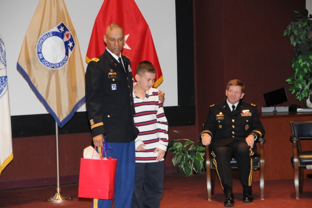 Col. Tommy Lancaster presents a gift to his son, TJ, during his retirement ceremony.