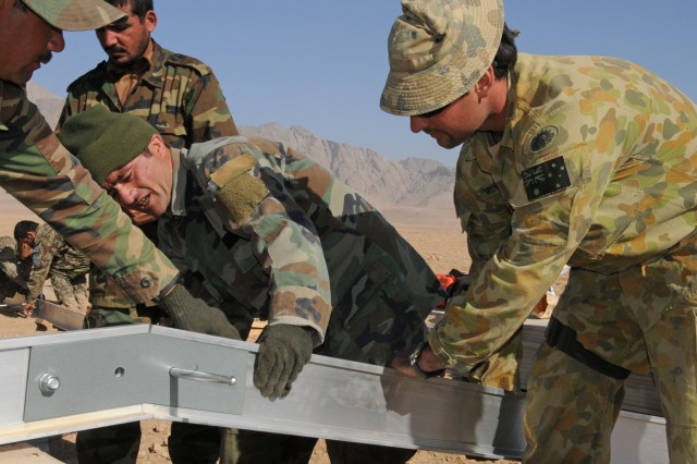 Afghan National Army (ANA) soldiers and Australian Capt. Jason Mildone, 2nd in command, Engineer Squadron, Mentoring Task Force 2, work together at the construction site of a new ANA patrol base in the Uruzgan Province of Afghanistan Nov. 13.