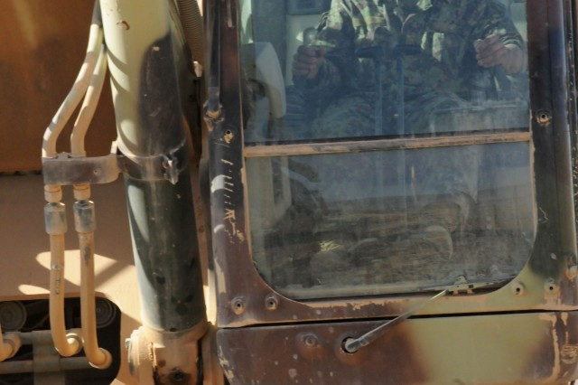 An Afghan National Army (ANA) engineer soldier drives a piece of construction equipment at the construction site of the new ANA patrol base in the Uruzgan Province of Afghanistan Nov. 13.