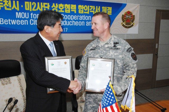DONGDUCHEON, South Korea - Col. Hank Dodge, U.S. Army Garrison Red Cloud commander, shakes hands with Dongducheon City Mayor Oh Sea-chang, after signing a community covenant memorandum of agreement for mutural cooperation between Dongducheon and the garrison at Dongducheon City Hall Nov. 17. In the covenant, the leaders of both communities agree to promote goodwill and friendship through a series of language, cultural exchange, volunteer and other events and social programs.