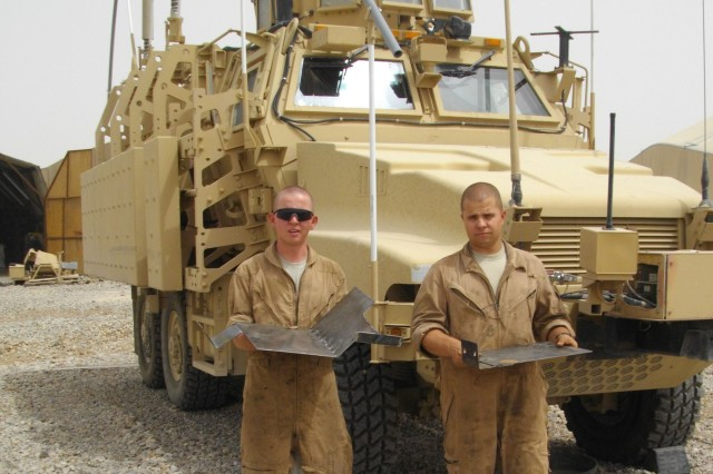Pfc. Aubrey Hanson, a wheeled vehicle mechanic, and Pfc. Brandon Schupman, a metal worker, both with the 64th Brigade Support Battalion, show off the mud guards that were designed to mitigate the amount of road debris damaging the Mine-Resistant Ambush-Protected vehicles.