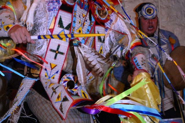 Adrian Primeaux performs a grass dance while Charley Lewis sings and drums at the Native American Heritage Month luncheon Nov. 18 at Hunt Lodge at Fort Leavenworth, Kan. The Haskell Indian Nations University students also demonstrated a prairie chicken and crow hop dances.