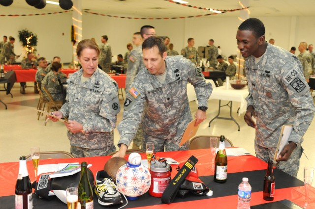 Brig. Gen. Robin B. Akin, the 3d Sustainment Command (Expeditionary) commanding general, Lt. Col. Tarpon S. Wiseman, the professor of military science with the University of Louisville Army Reserve Officers Training Corps, and Cadet Jamie Jackson, the UofL Cardinal Battalion commander, judge decorated tables during the battalion's dining-in.  (U.S. Army photo by Sgt. Michael Behlin)