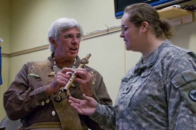 """Dressed in American Native wear, Tim Timothy, a member of the Muscogee Creek nation shows Spc. Denielle Podraza how to play the authentic ceremonial flute he made. Podraza plays a piccolo in the 208th Army Reserve band.  Timothy spoke to an audience of about 60 people at the 81st Regional Support Command's observance of Native American Heritage Month, Nov. 23.  Timothy spoke to raise  awareness of creek people's culture and said that the correct term should be more aptly described as """"American Native"""" rather than the other way around."""