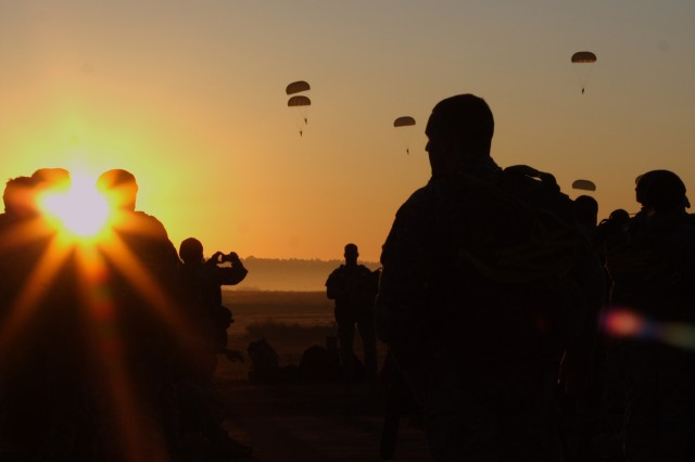 The sun rises over Sicily Drop Zone at Fort Bragg as USACAPOC(A) paratroopers get ready to board aircraft for their airborne operation at Operation Toy Drop last year.