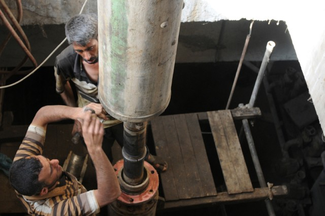 Workers make adjustments to a pump shaft at a station in Numaniyah. The pumping station in Numaniyah recently received upgrades to its old pumps and new pumping equipment to increase its water flow into local farmland.