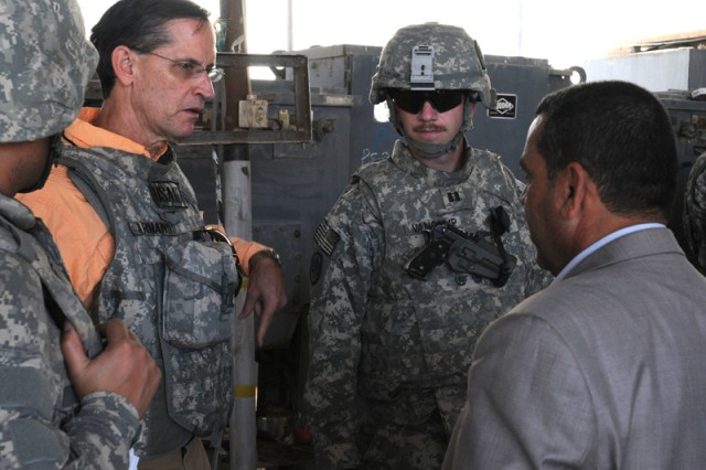 Armand Lanier, an agricultural advisor to the Wasit Provincial Reconstruction Team and Capt. David VanCamp, commander of Company H, 2nd Squadron, 3rd Armored Cavalry Regiment, talk with a local Iraqi farmer. Lanier, escorted by members of Company H, met with local farmers to discuss responsible water use and future agricultural production.