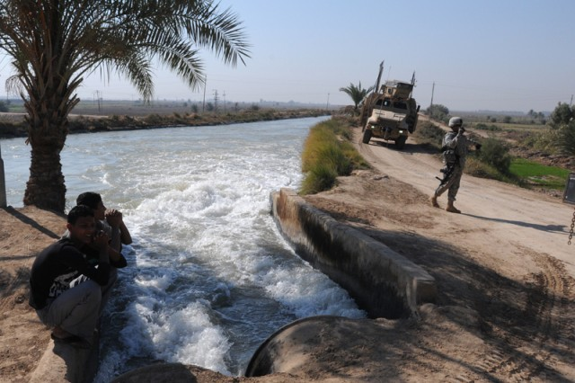 Local Iraqi boys watch as water flows freely from the Tigris River into an irrigation canal. The water is delivered through a pump station and feeds 1,500 area farms.