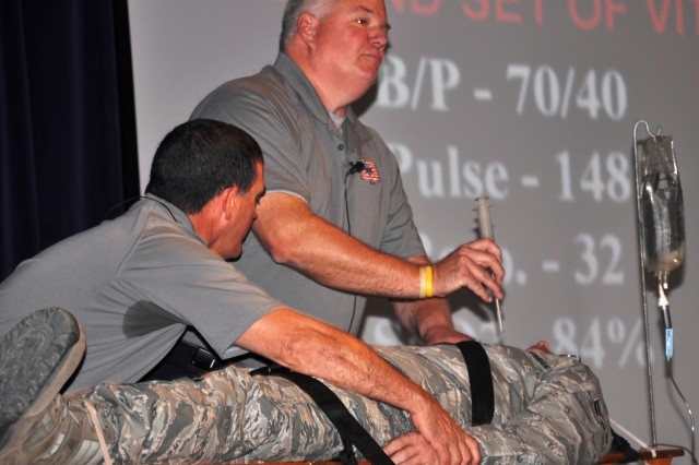 Ronny Garcia and Greg McCarty demonstrate lifesaving techniques on Airman 1st Class Chris Kilbourne during the Street Smart presentation.
