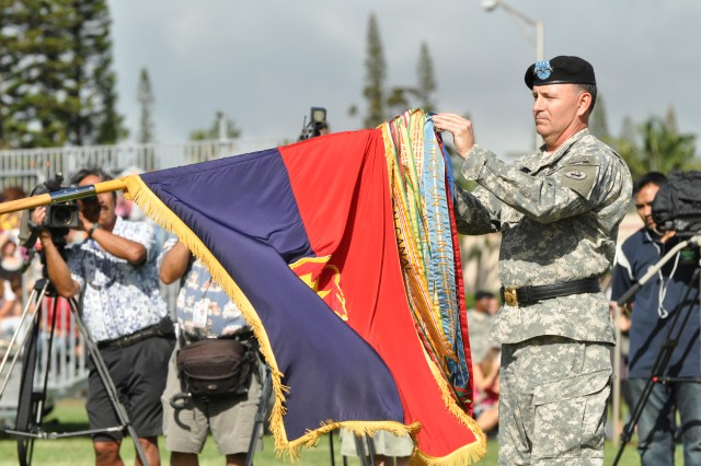 "Lieutenant Gen. Benjamin R. Mixon, commanding general, U.S. Army Pacific, affixes an Iraqi Surge Campaign Streamer onto the division colors, honoring the 25th Infantry Division's service in northern Iraq during the ""Troop Surge"" from summer 2006 to early 2007, during the 25th Inf. Div. Deployment Ceremony, held on Schofield Barracks, Hawaii, Nov. 24. Mixon commanded the division during this period of time and expressed his honor to award the collective efforts of the Tropic Lightning Division Soldiers during this tour of duty. (U.S. Army photo by Sgt. Jesus J. Aranda, 25th Infantry Division Public Affairs Office)"