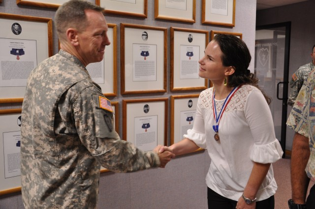 """Kathleen Ramsden, the curator for the """"Tropic Lightning Museum,"""" is congratulated by Maj. Gen. Bernard S. Champoux, commanding general, 25th Infantry Division, for her contributions to preserving and promoting the division's storied legacy through her work managing the post museum, during an award ceremony at Schofield Barracks, Hawaii, Nov. 24. (U.S. Army photo by Sgt. Jesus J. Aranda, 25th Infantry Division Public Affairs Office)"""