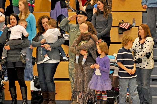 Soldiers and families stand for the national anthem during the homecoming event in the Wiesbaden Fitness Center Nov. 23.