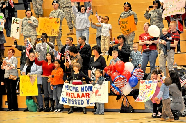 Families cheer and wave as 1st Armored Division Soldiers arrive home from Iraq.