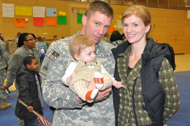 Maj. Jacob Skugrud is greeted by his wife Tahroma and child at the Wiesbaden Fitness Center during the welcome home event.