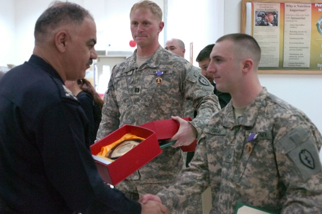 Capt. Anthony Smith, Commander of Company A, 1st Battalion, 14th Infantry Regiment, and Pfc. Matthew Gray, a radio and telephone operator, Company D, 1st Bn., 14th Inf. Reg., received plaques from the Iraqi Police after receiving Purple Hearts in a Thanksgiving Day ceremony.