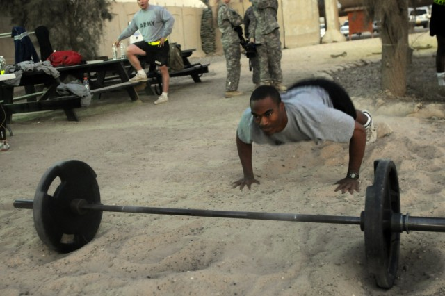 Captain Dhyan Tarver, the air defense, air space cell management planner for HHC, 1st AAB, 3rd ID, concentrates while doing a push-up for the Raider Brigade Supports the Wounded Warrior Project Workout/Run on Camp Liberty, Nov. 21.