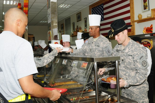 Maj. Gen. Vincent Brooks (2nd from right), 1st Infantry Division and U.S. Division-South Commanding General, serves a Thanksgiving meal alongside officers from the 3rd Armored Cavalry Regiment at Camp Delta in southern Iraq. Brooks and other senior leaders of the Big Red One visited 23 dining facilities on 20 posts spread over nine provinces in southern Iraq to spread holiday cheer.