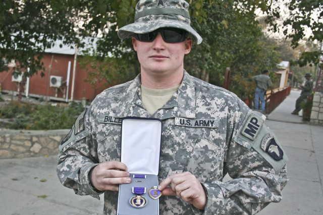 Sgt. Timothy Billett, Headquarters and Headquarters Company, 1st Special Troops Battalion, a military policeman from Wyoming, Mich., displays the Purple Heart he received from his father, Sgt. William Billett, an infantryman with Company B, 2nd Battalion, 506th Infantry Regiment Thanksgiving Day on Forward Operating Base Finley Shields in eastern Afghanistan.