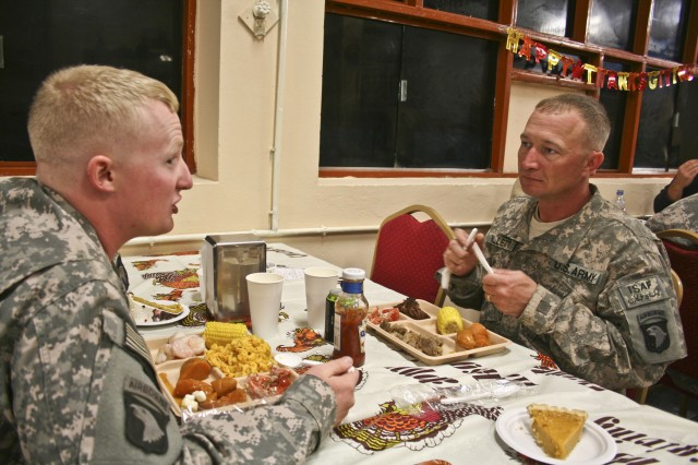 Sgt. William Billett (right), an infantryman with Company B, 2nd Battalion, 506th Infantry Regiment, eats Thanksgiving dinner with his son, Sgt. Timothy Billett, a military policeman from Headquarters and Headquarters Company, 1st Special Troops Battalion, a couple hours after pinning the Purple Heart on his chest Nov. 25 on Forward Operating Base Finley Shields in eastern Afghanistan.