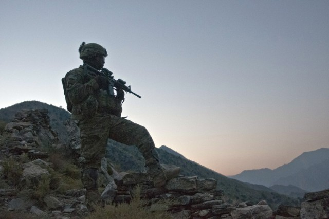 """KUNAR PROVINCE, Afghanistan - As the sun begins to rise, U.S. Army Staff Sgt. McCarthy Phillip, an infantry squad leader from Decatur, Ga., assigned to Company C, 1st Battalion, 327th Infantry Regiment, Task Force Bulldog, scans the Pech River Valley for insurgent movement in eastern Afghanistan's Kunar Province Nov. 20. """"We're up here doing an over watch and trying to stop any type of movement in the trails,"""" said Phillip. (Photo by U.S. Army Staff Sgt. Mark Burrell, Task Force Bastogne Public Affairs Office)"""
