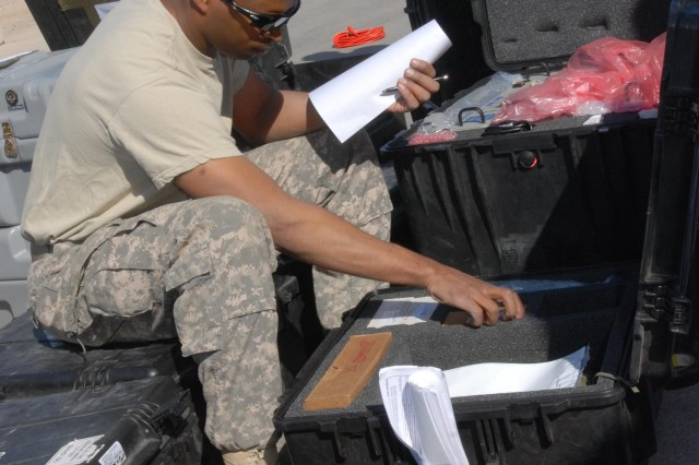 Sgt. 1st Class Earl Brown, a telephone communications officer with Signal Company, Division Headquarters and Headquarters Battalion, 1st Infantry Division, inventories boxes in Basra Nov. 27. The inventory is a necessary part of the process of getting DHHB, its equipment and its Soldiers back to Fort Riley, Kan.