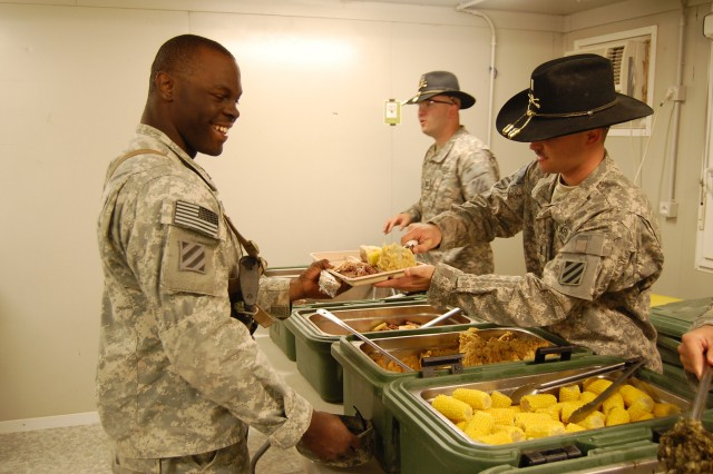 CONTINGENCY OPERATING SITE MAREZ, Iraq- 1st Lt. Timothy Mahoney (right), from Darlington, S.C., the executive officer for A Troop, 6th Squadron, 8th Cavalry Regiment, serves one of his Soldiers Thanksgiving chow at a remote checkpoint in northwestern Iraq, Nov. 25.