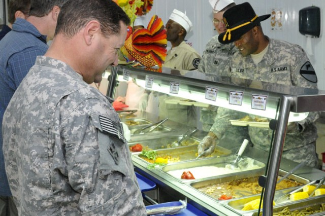 "CONTINGENCY OPERATING SITE IRBIL, Iraq-Command Sgt. Maj. Calvin Coler (right), 5th Battalion, 82nd Field Artillery, 4th Advise and Assist Brigade, 1st Cavalry Division, serves Thanksgiving Day dinner to Soldiers stationed here. ""We have a small element here,"" said Coler.  ""But that doesn't mean they don't matter.  I'm here to show the Soldiers that we know they're here and we're taking care of them.""  The Black Dragon battalion recently deployed in support of Operation New Dawn and is celebrating their first major holiday away from Families."